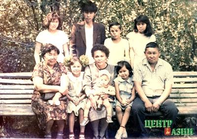 Наша большая семья Бегзи на прогулке. Слева направо в первом ряду: тетя Надя Очирова, сестра мамы, моя сестра Туяна, мама Ханда Араднаевна, на ее коленях сестра Саяна, сестра Яна, папа Шайгожап Тюлюшевич. Во втором ряду: сестра Надя, братья Коля, Андрей и я – Альфина. Национальный парк. Кызыл. Лето 1987 года.
